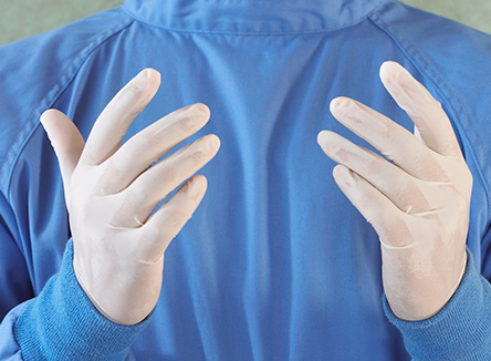 The Gloved hands of a surgeon.