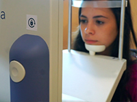 A young woman staring an eye box screen with her chin on a stand