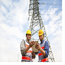 Two engineers in front of a pylon