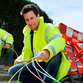 Workers with fibre coil on the road.