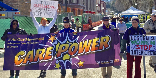 Women holding a purple 'Care Power' banner at the Portland Womxn's March