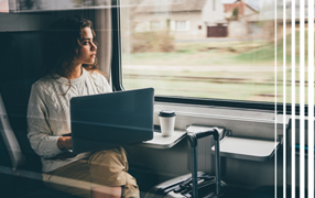 Woman on train with laptop looking out window