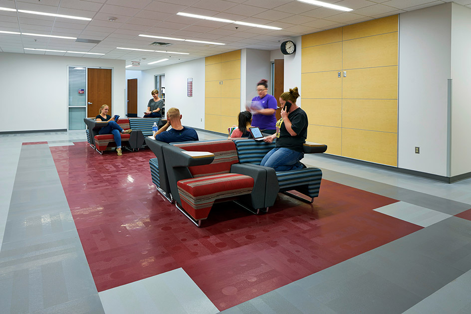 Students using tablets and cell phones on lounge furniture