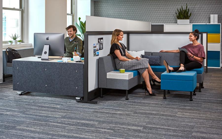 People talking in lounge seating, man working at desk