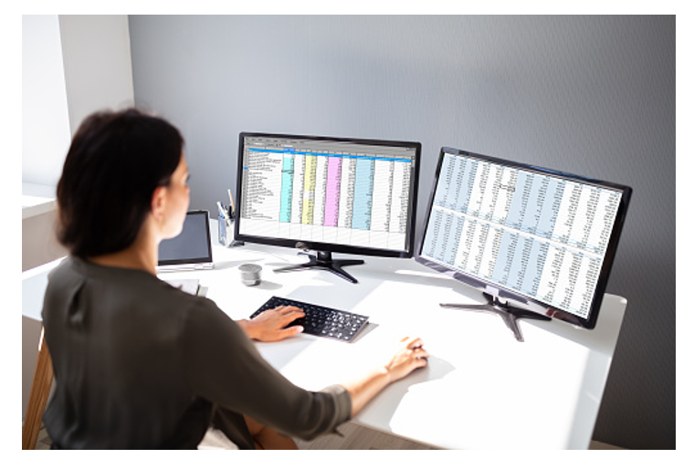 Woman Working on Spreadsheets With Two Monitors