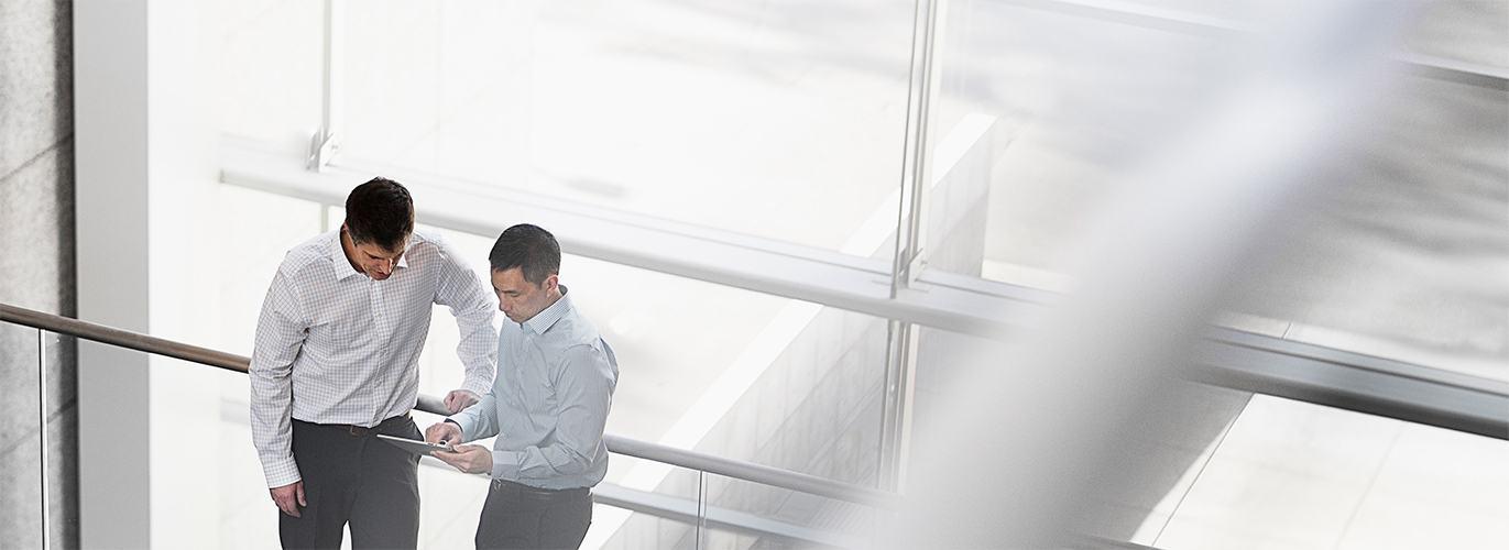 Two men in hallway looking at ipad