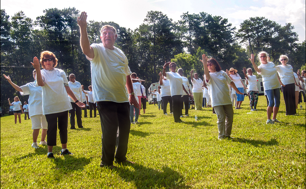 Group of older adults practicing Tai Chi in the park.