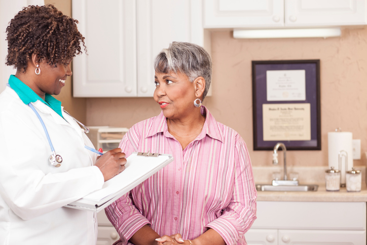 An older woman talking to a doctor.