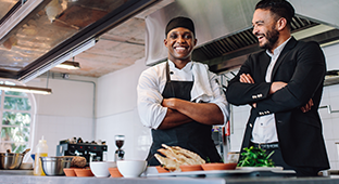 Deux hommes souriants dans une cuisine