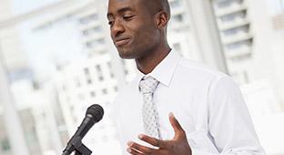 Un étudiant en relation publique fait une présentation devant un micro