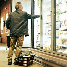 Man in the grocery store opening fridge.
