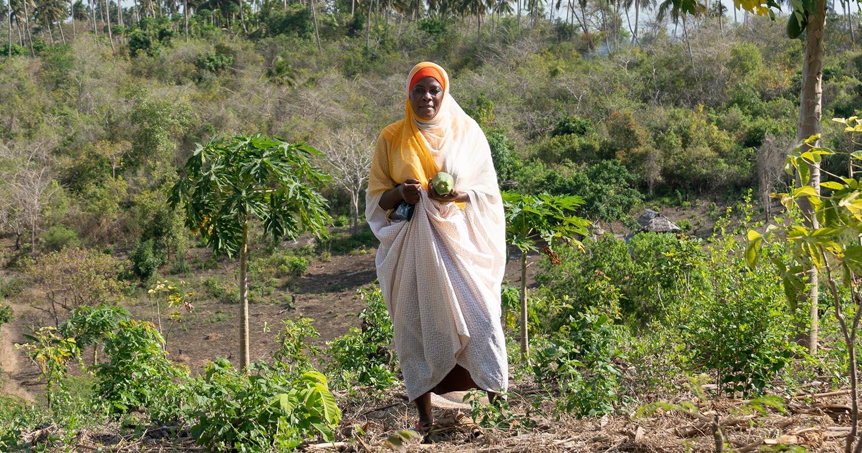 Latifah standing on her farm in Tanzania