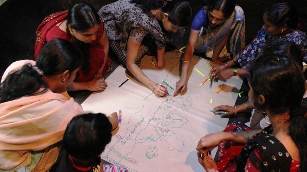 Women gather around to draw a community map.