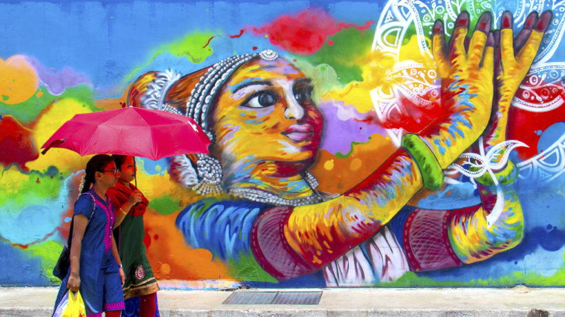 Two woman walking in front of a colorful mural in India. Photo credit PRRC India