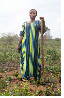 Fatuma standing on a hillside farm in Tanzania.