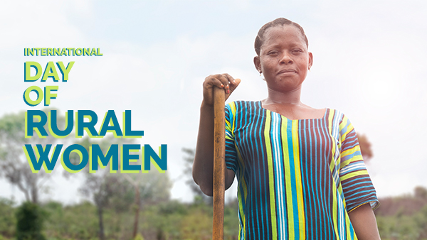 Fatuma standing in her field with the words 'International Day of Rural Women' written to the left