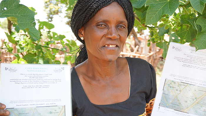 Woman in Zambia holds up her new land documents.