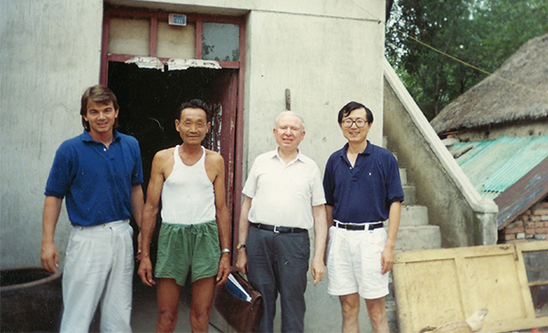 Li Ping alongside Tim Hanstad, Roy Prosterman, and a farmer in China