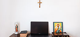 Computer on desk with cross in background