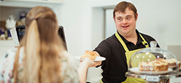 Man with Down syndrome serving at a cafe