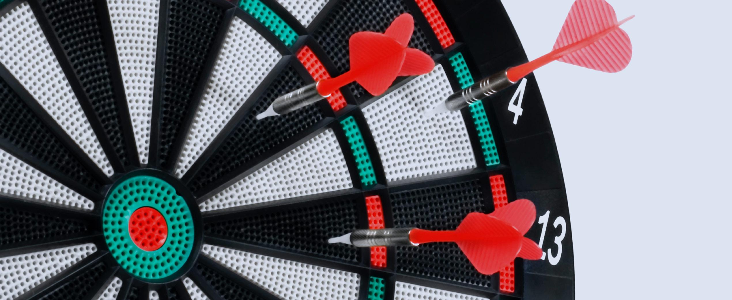 Dart board with darts away from the bullseye.