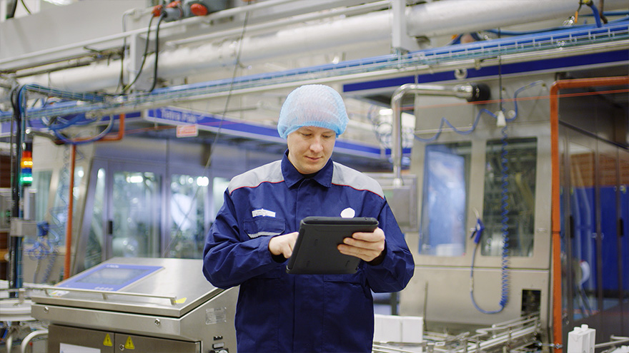 Factory worker in blue coat looking at ipad