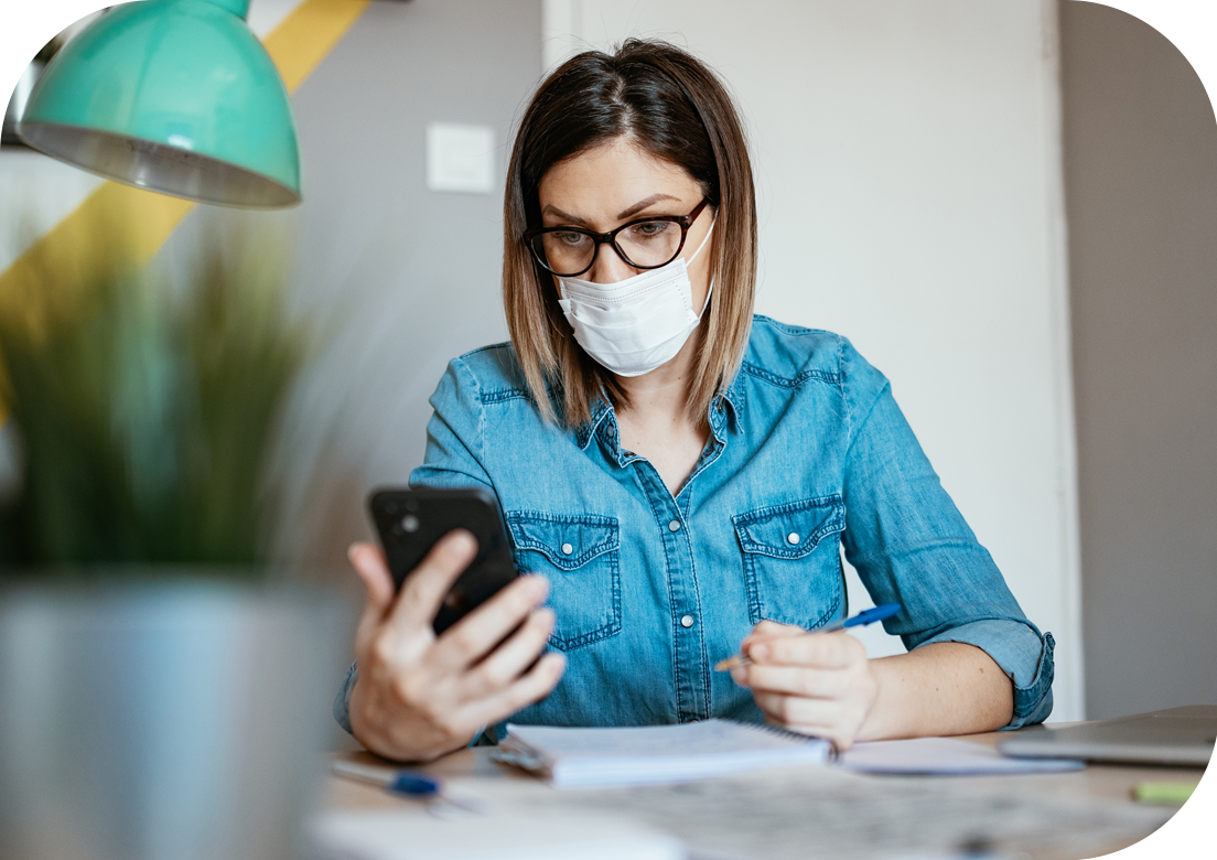 Person wearing mask looking at mobile phone in hand